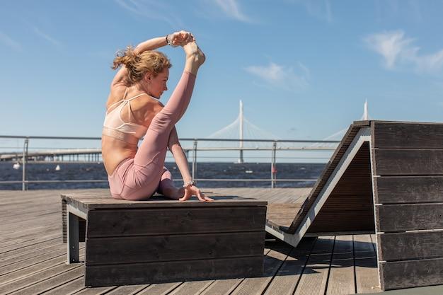Atleta feminina se virou para a câmera enquanto praticava ioga no terraço de madeira em um dia ensolarado
