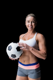 Atleta feminina segurando uma bola de futebol em preto