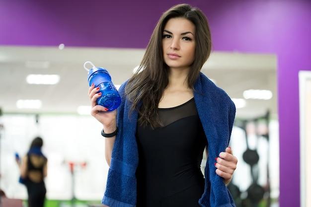 Atleta feminina segurando uma garrafa de água com uma toalha em volta do pescoço