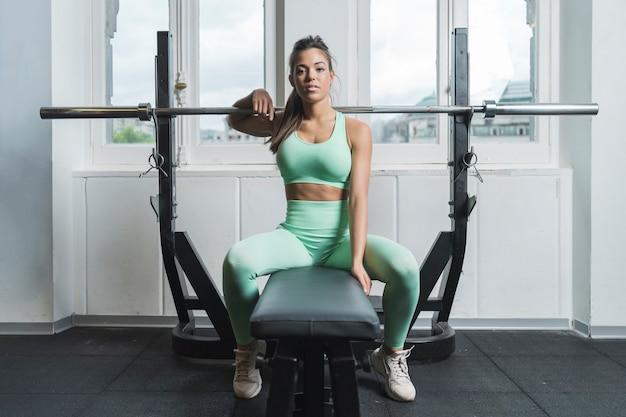 Atleta feminina, sentada em um banco de uma academia e olhando para a câmera. ela está vestindo roupas esportivas verdes. ela está penteando o rabo de cavalo