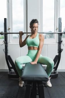 Atleta feminina sentada em um banco em uma academia e olhando para baixo. ela está vestindo roupas esportivas verdes. ela está penteando o rabo de cavalo