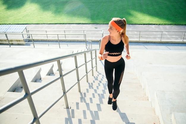 Atleta feminina subindo as escadas de um estádio. mulher em fitness wear fazendo exercícios correndo nas escadas ao lado dos assentos de um estádio.