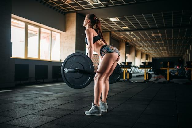 Atleta feminina treinando com peso no ginásio de esportes