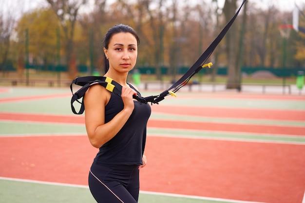 Atleta feminina treinando usando trx no campo esportivo