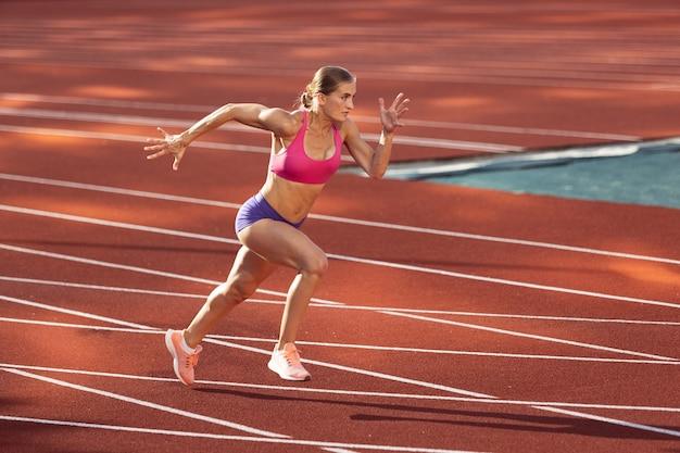 Atleta feminina, uma mulher caucasiana, corredora praticando sozinha em um estádio público