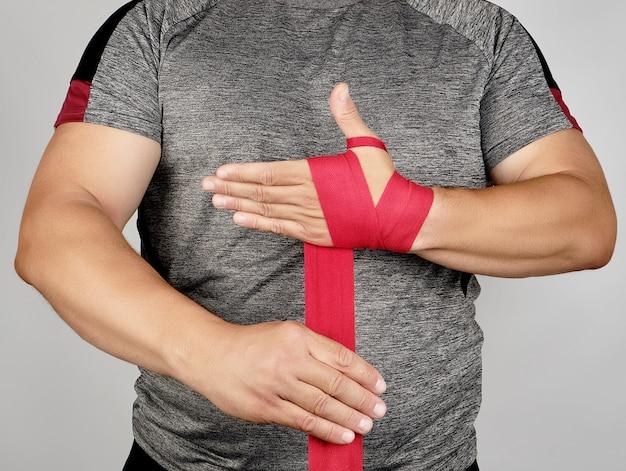 Atleta fica em roupas cinza e envolve as mãos em bandagem elástica têxtil vermelha