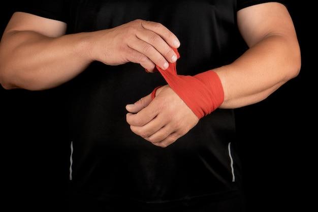 Atleta fica em roupas pretas e envolve as mãos em bandagem elástica têxtil vermelha