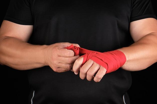 Atleta ficar em roupas pretas e enrole as mãos na bandagem elástica têxtil vermelho antes do treino