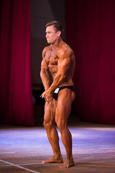 Atleta fisiculturista demonstra músculos abdominais e tórax em competições