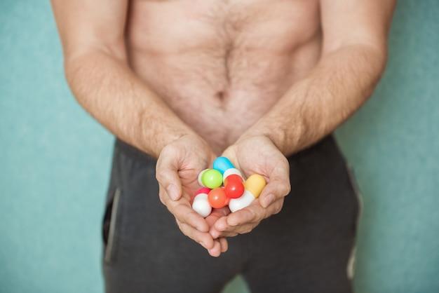 Atleta fisiculturista toma drogas na forma de comprimidos farmacêuticos rápido progresso no desenvolvimento muscular