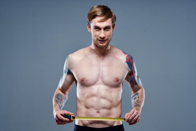Atleta fofa com tatuagem de fisiculturista modelo de fitness com fita centímetro no braço.