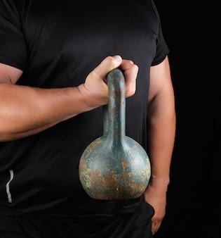 Atleta forte adulta em roupas pretas, segurando um kettlebell de ferro