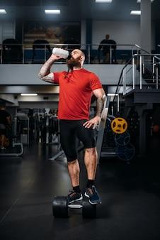Atleta forte bebe água após o exercício com halteres, treino no ginásio.