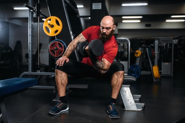 Atleta forte com halteres em ação, treino no ginásio