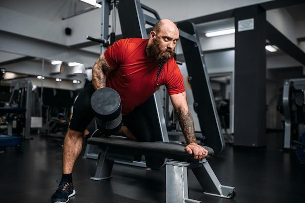 Atleta forte com halteres em ação, treino