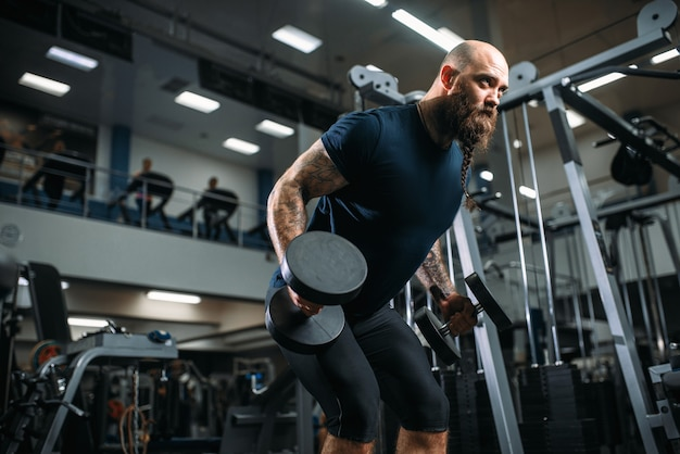 Atleta forte com halteres, treinando na academia