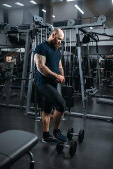 Atleta forte com halteres, treinando na academia.