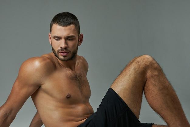 Atleta forte e adorável descansando após um treino duro isolado em um fundo cinza