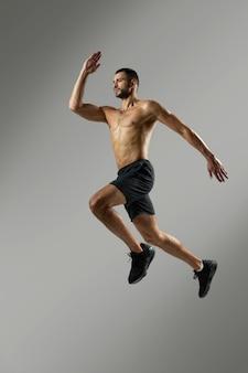 Atleta forte e bonito em roupas esportivas se aquecendo na sala dentro de casa