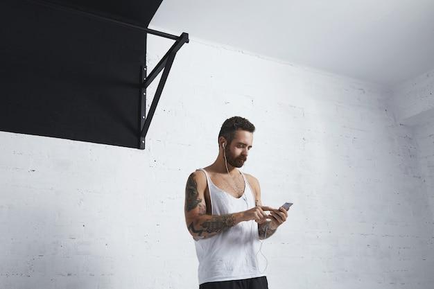 Atleta forte e tatuado com smartphone e fones de ouvido escolhe uma lista de reprodução de música antes do treino, ao lado da barra de puxar na academia