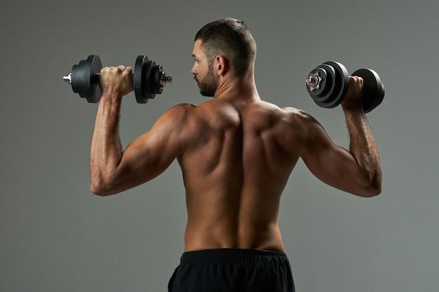 Atleta forte em roupa esportiva preta, posando para a câmera fotográfica na sala dentro de casa