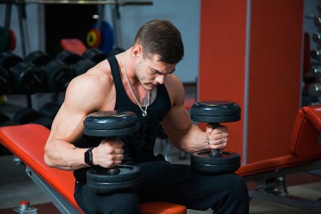 Atleta forte segurando halteres pesados