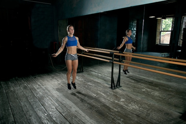 Atleta garota pulando corda em frente a um espelho no ginásio