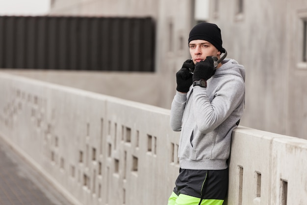 Atleta, headphone, inclinar-se, contra, parede
