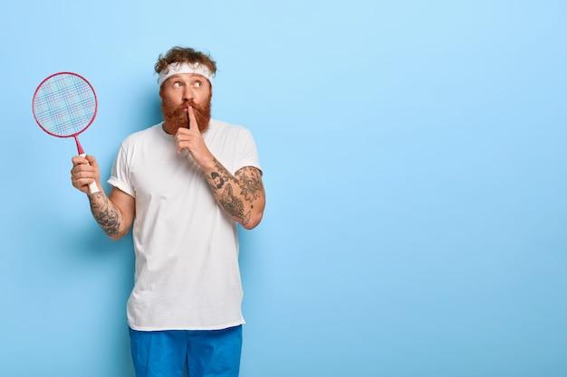 Atleta hipster com raquete de tênis na mão, faz sinal de silêncio, usa roupa esporte, conta segredo