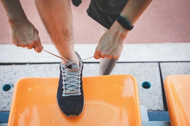 Atleta homem correndo na pista de estrada, exercício treino bem-estar e corredor amarrar cadarços