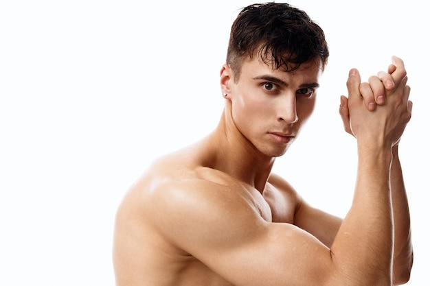 Atleta homem juntou as mãos perto do rosto em um fundo claro