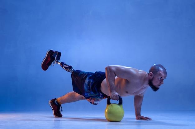 Atleta incapacitado amputado isolado no fundo azul do estúdio