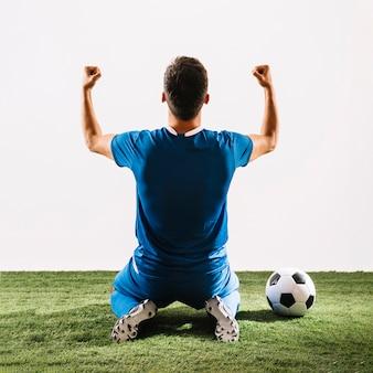 Atleta irreconhecível, regozijando-se sobre a vitória no campo