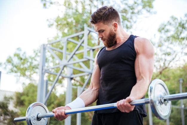 Atleta jovem barbudo sério fazendo exercícios e levantando barra ao ar livre