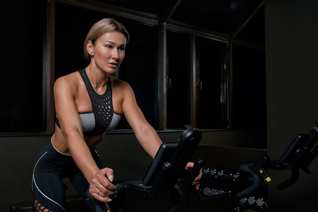 Atleta jovem confiante mulher exercitando na bicicleta dentro de casa. a menina atrativa determinada da aptidão que faz ciclismo exercita no gym escuro. treino funcional de garota esportiva. treinamento cardíaco