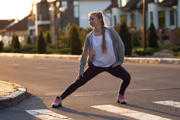 Atleta jovem corredor feminino está correndo na rua da cidade ao sol. linda mulher caucasiana