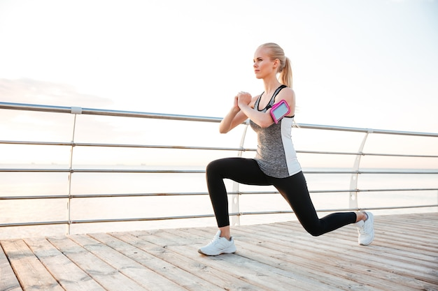 Atleta jovem e atraente em pé e esticando as pernas no cais