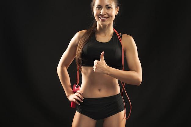 Atleta jovem e musculosa com uma corda de pular no preto