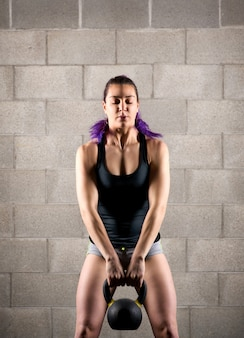 Atleta jovem exercitando com um kettlebell
