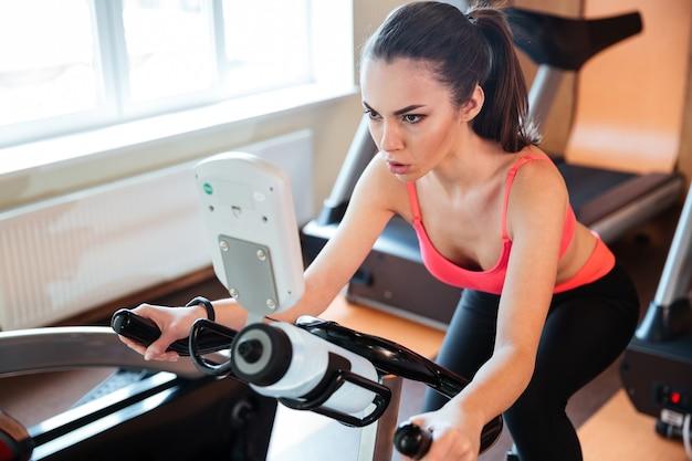 Atleta jovem muito concentrada malhando de bicicleta na academia
