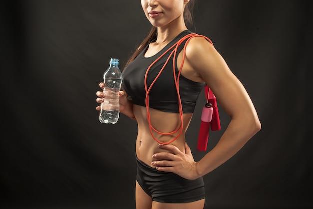 Atleta jovem muscular com uma corda de pular no preto