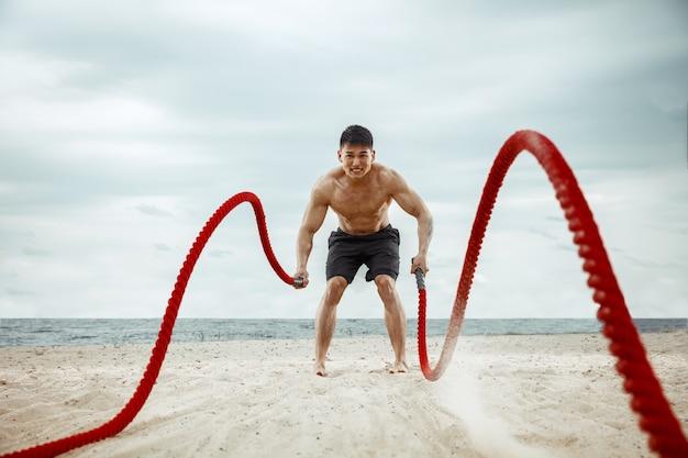 Atleta jovem saudável fazendo agachamentos na praia