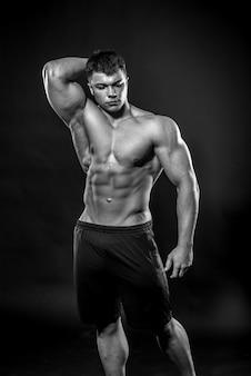 Atleta jovem sexy, posando em preto no estúdio. fitness, musculação, preto e branco.