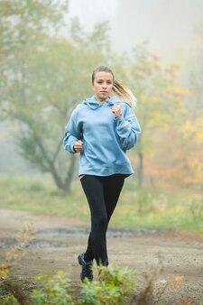 Atleta loira com um moletom azul, perneira preta e tênis correndo ao longo do caminho da floresta entre as árvores em uma manhã de nevoeiro de outono