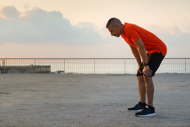 Atleta macho cansado tendo uma ruptura depois de correr