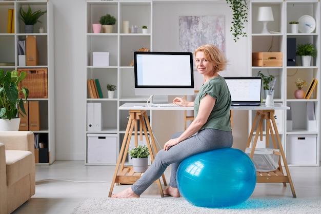Atleta madura em roupas esportivas, olhando para você enquanto está sentado no fitball em frente à tela do computador e surfando para um treino online
