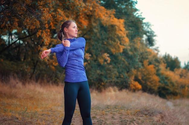Atleta magra e caucasiana com camisa azul e leggins esportivos pretos aquece antes de correr