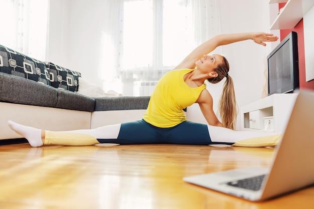 Atleta magra em forma, sentada em pose de perna larga, alongando e acompanhando a aula online