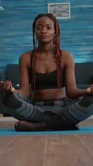 Atleta magro, mulher, colocando-se em posição de lótus no mapa de ioga durante um treino matinal de fitness na sala de estar, aproveitando um estilo de vida saudável