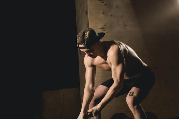 Atleta martelando pneu de caminhão com uma marreta durante treino